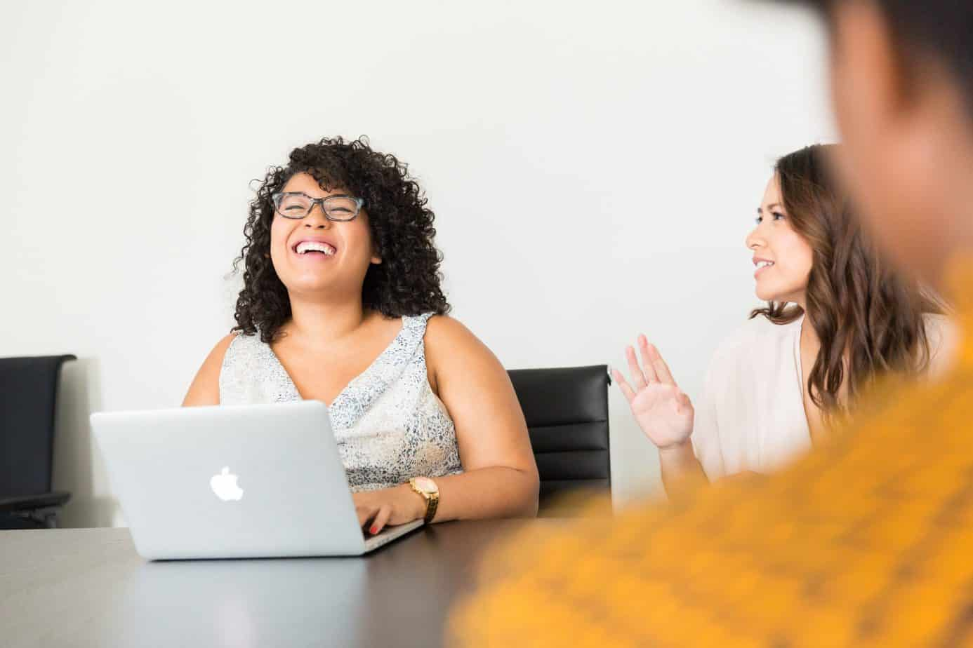 Smiling women working on a laptop