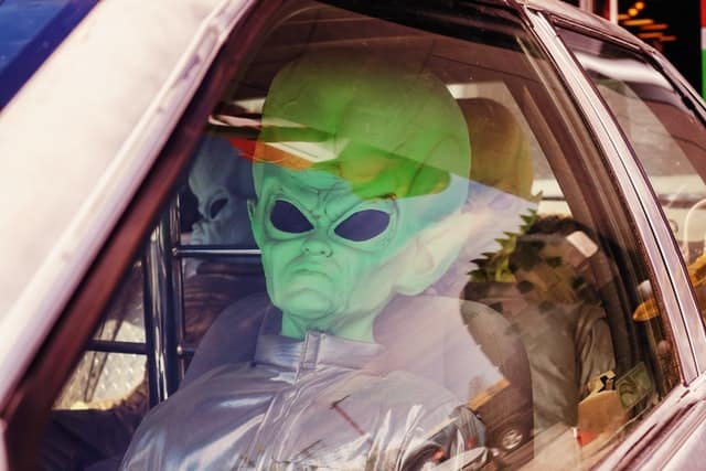 Alien from outer space riding in a car